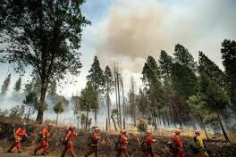 Inmate firefighters battle the Ferguson fire in Jerseydale, California, on July 22, 2018. - A fire that claimed the life of one firefighter and injured two others near California's Yosemite national park has almost doubled in size in three days, authorities said Friday. The US Department of Agriculture (USDA) said the so-called Ferguson fire had spread to an area of 22,892 acres (92.6 square kilometers), and is so far only 7 percent contained. (Photo by NOAH BERGER / AFP)        (Photo credit should read NOAH BERGER/AFP/Getty Images) *** BESTPIX ***