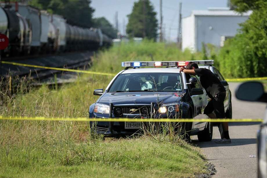 Conroe police officers speak with bystanders at the scene where a man was fatally struck by a train on Monday, July 23, 2018, in Conroe. Photo: Michael Minasi, Staff Photographer / Houston Chronicle / © 2018 Houston Chronicle