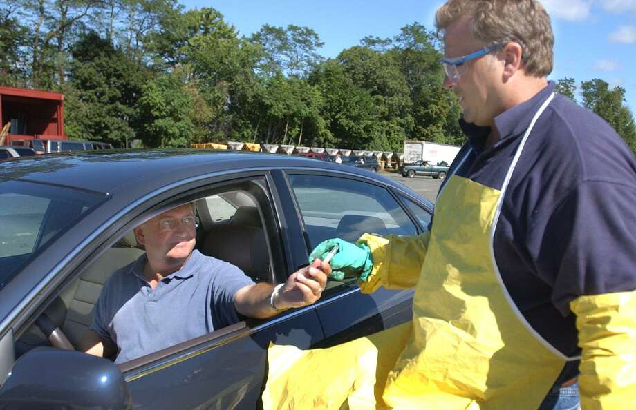 Ron Kanode of Ridgefield hands a mercury themometer to hazardous wastes worker, Mike Corrado. ARea residents dumped off all manner of household debris  yesterday at the Danbury Publicv Works Department annual Household Hazardous Waste Collection Day. Photo: File Photo\Wendy Carlson / File Photo / The News-Times File Photo