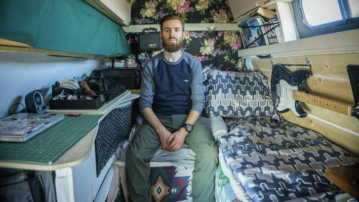 Tyler Finlay in his converted Ford E350 hightop old work van, in which he lives, in Vancouver.