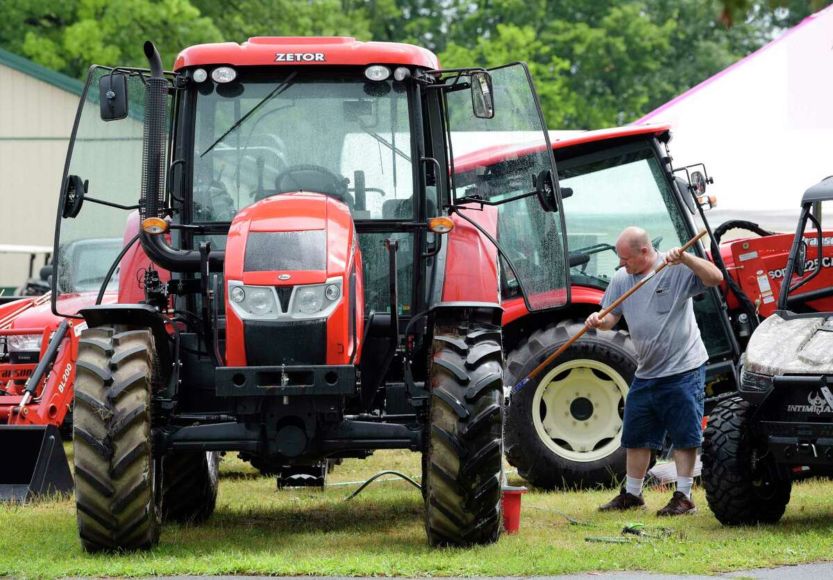 John Cipperley, owner of JC Tractors out of Hoosick Falls washes one of his Zetor agricultural tractors at the Saratoga County Fair grounds on Monday, July 23, 2018, in Ballston Spa, N.Y. The fair opens on Tuesday. (Paul Buckowski/Times Union)