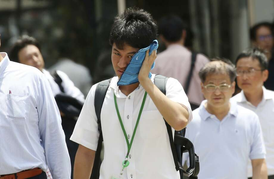 A man wipes the sweat from his face in the scorching heat at a business district in Tokyo, Monday, July 23, 2018. Searing hot temperatures are forecast for wide swaths of Japan and South Korea in a long-running heat wave. The mercury is expected to reach 39 degrees Celsius (102 degrees Fahrenheit) on Monday in the city of Nagoya in central Japan and reach 37 in Tokyo. Deaths have been reported almost every day. (AP Photo/Koji Sasahara) Photo: Koji Sasahara, Associated Press