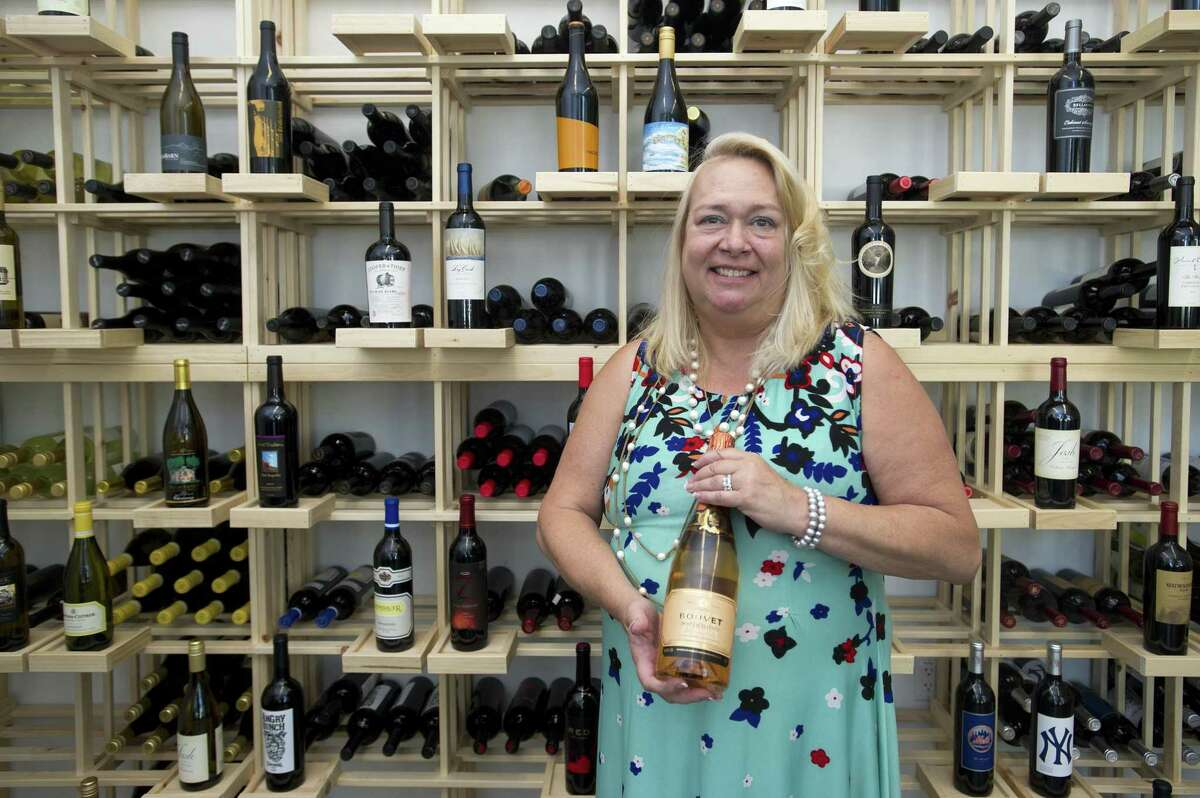 """Harbor Point Wines & Spirits owner Theresa """"Terry"""" Rogers poses inside her new store at 130 Washington Blvd., in the South End of Stamford, Conn., on Monday, July 16, 2018."""