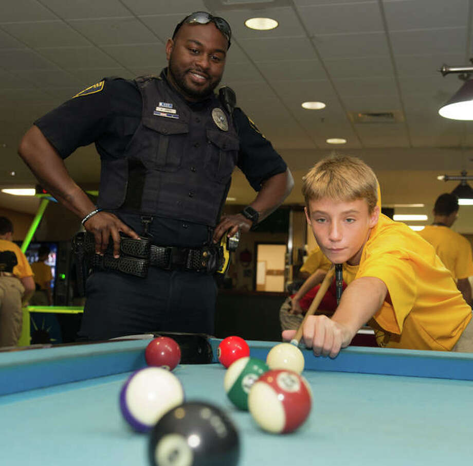 SIUE Police Officer Anthony Jones looks on with encouragement as Team Illinois Youth Police Camp cadet Elijah Duke, of Alton, plays pool. Photo:       For The Telegraph