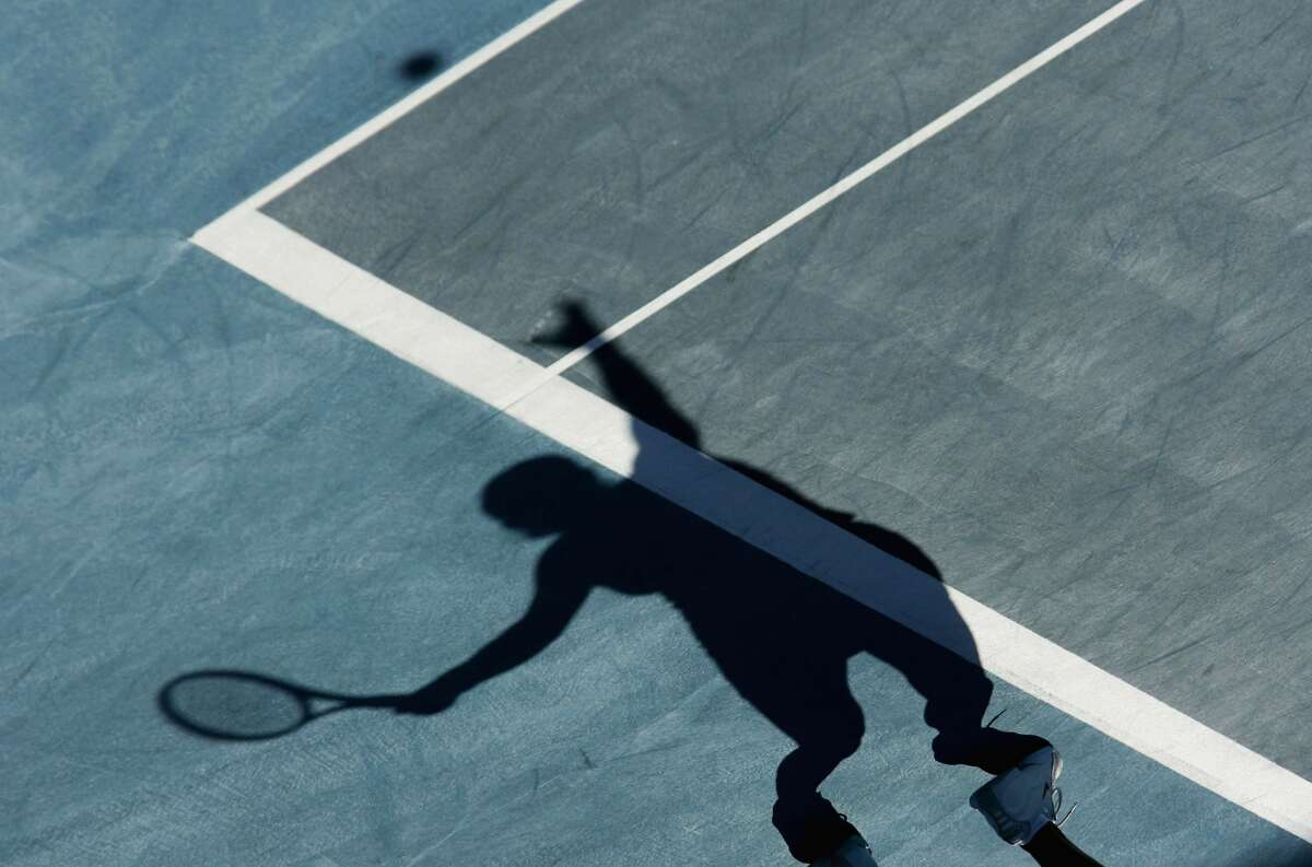 In this file photo, the shadow of Amelie Mauresmo of France is seen on the court as she serves to Conchita Martinez of Spain during their women's singles tennis match during the Athens 2004 Summer Olympic Games.