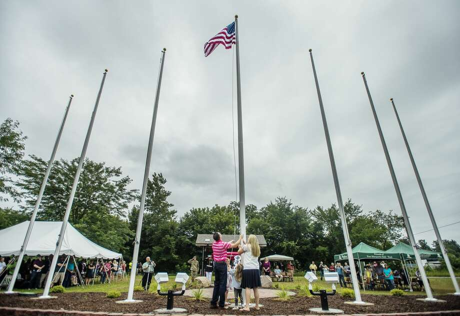 Lindsey Elias, Ryan Burgess' sister, along with Ryan's niece, Ainsley Elias, Ryan Maciejewski and Kayla Maciejewski raise the American flag during a dedication ceremony for the new Sanford Flag Memorial on Saturday, July 21, 2018 in Sanford. The planning and creation of the memorial was the work of John and Kim Burgess, who lost their son, Lance Cpl. Ryan Burgess, on Dec. 21, 2006 in Iraq. (Katy Kildee/kkildee@mdn.net) Photo: (Katy Kildee/kkildee@mdn.net)