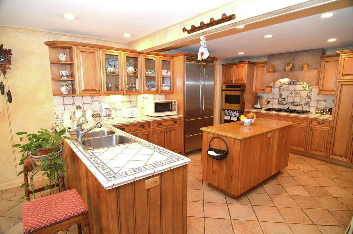The eat-in kitchen has been equipped with high-end appliances, including a six-burner Viking cooktop, two ovens and an oversized Liebherr refrigerator. French doors in the breakfast room open out to the home's private backyard deck.