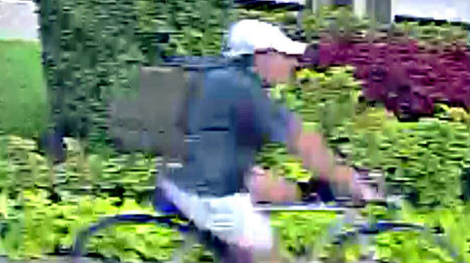 Surveillance photos released by the Houston Police show a suspect wanted in the killing of Dr. Mark Hausknecht on Friday, July 20, 2018. The suspect is described as wearing a blue, short-sleeved polo shirt, a khaki ball cap and khaki shorts at the time of the shooting. He carried a large, olive green backpag,. Photo: Houston Police Department