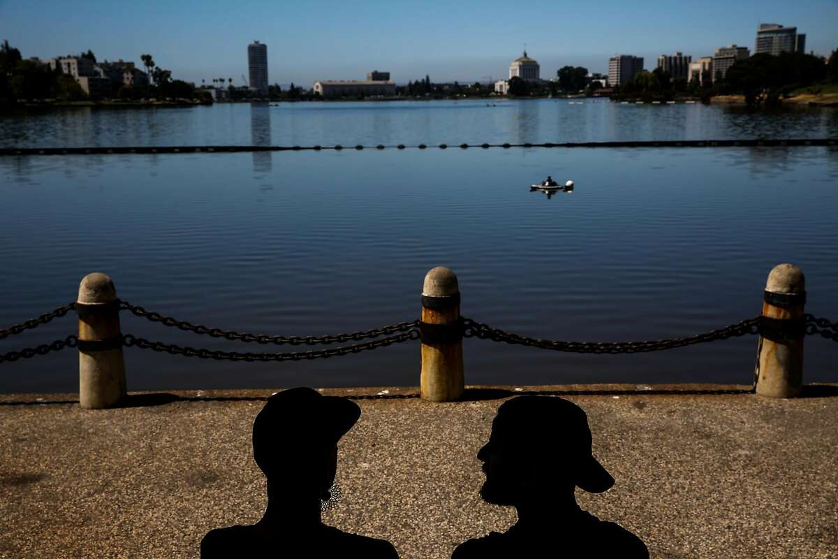 Friends Gabriel (left) and Nick chat in the shade at Lake Merritt in Oakland, California, on Monday, July 23, 2018.