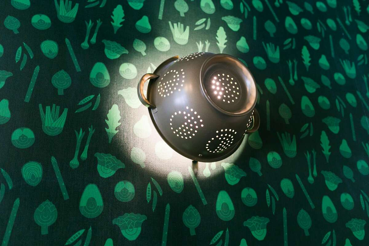 A colander acts as a decorative light fixture in the the Salad Lounge at Mixt on Valencia Street in San Francisco, Calif. on Friday, July 20, 2018.