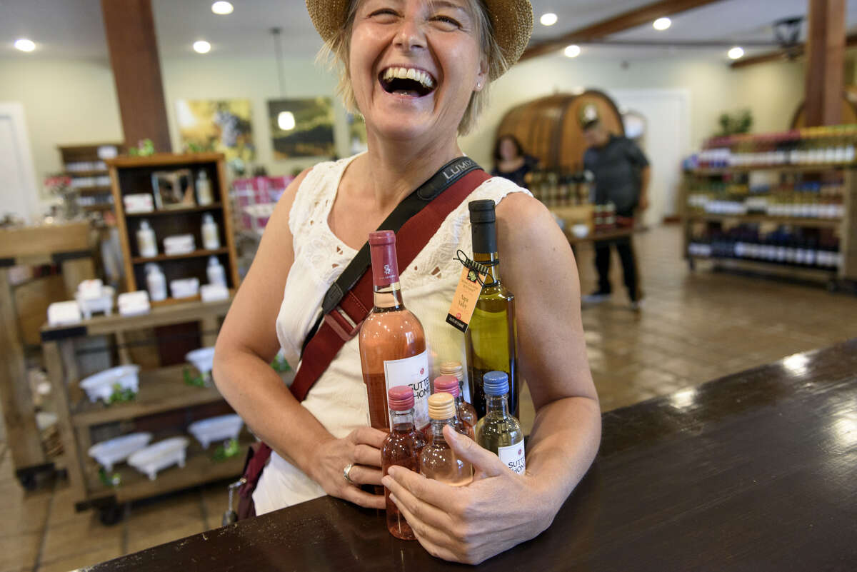 Monika Renzler, visiting from Germany, has her hands full of bottles she is buying at SutterHome's tasting room in St Helena, Calif., on Friday July 20, 2018.