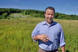 Supervisor Chris Koetzle at the former landfill above the natural hillside bowl, upper left, that is the proposed site of a Glenville Police training range Tuesday June 19, 2018 in Glenville, NY.  (John Carl D'Annibale/Times Union)