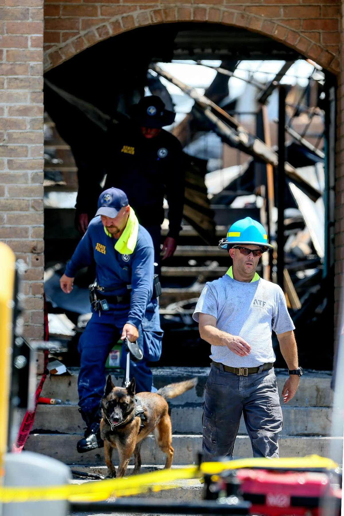 Investigators walk through an entryway at the Iconic Village Apartments in San Marcos on Monday, July 23, 2018. Four victims have been recovered so far from the fire that began at the apartment complex at 4:30 a.m. and affected three apartment buildings on Friday, July, 20. Five people are still unaccounted for. Officials do not yet know the origin of the fire, how it started. or what the total number of victims will be.