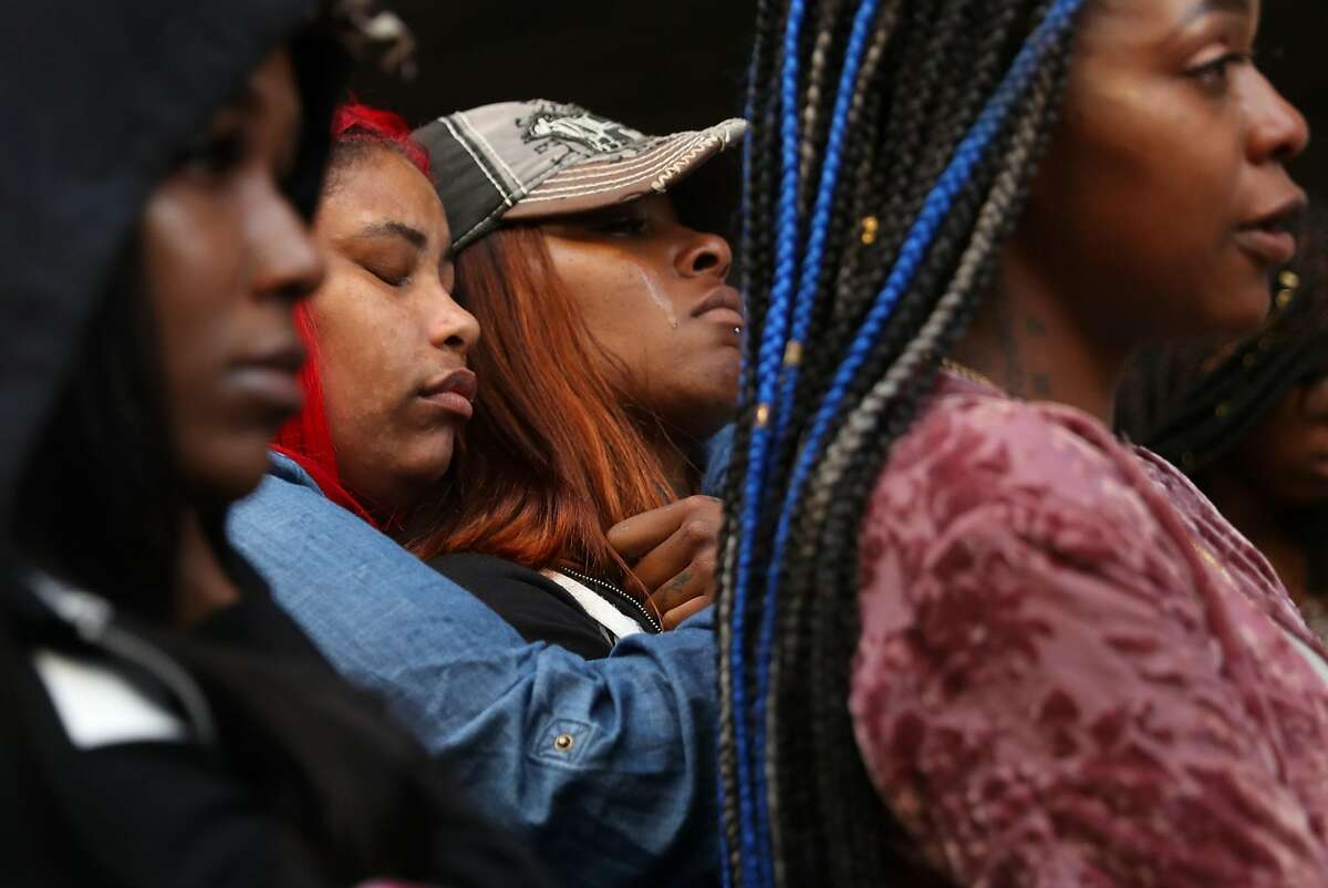 Friends of Nia Wilson mourn during a vigil in memory of the 18-year-old stabbing victim at McArthur BART Station in Oakland, Calif. on Monday, July 23, 2018.