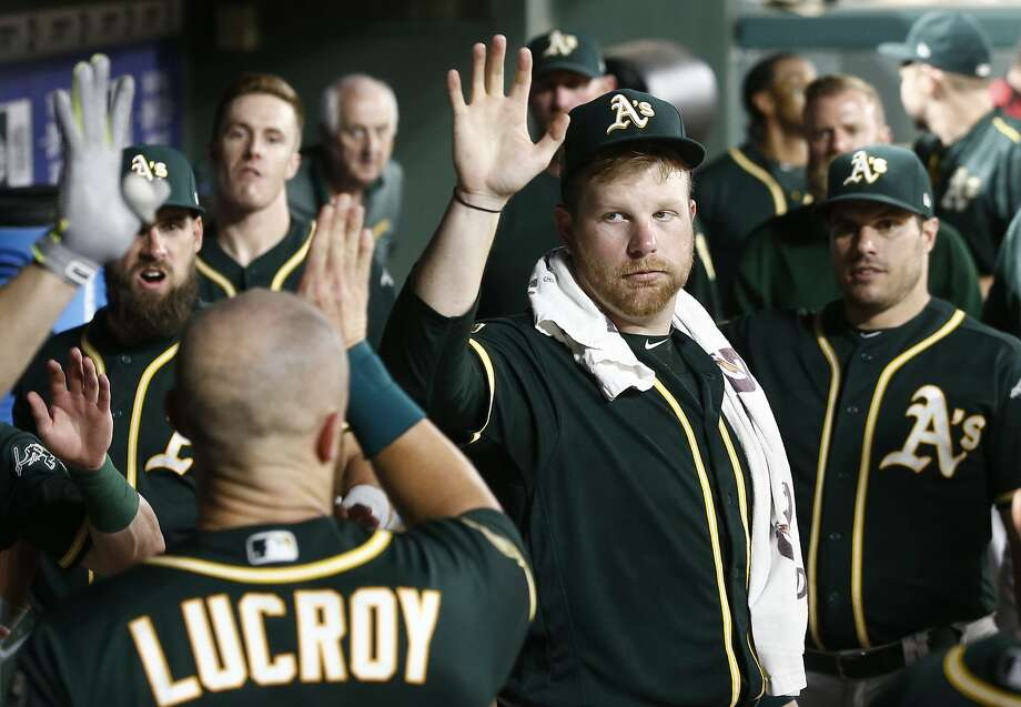 Oakland Athletics starting pitcher Brett Anderson, center, congratulates Jonathan Lucroy after he scored against the Texas Rangers during the seventh inning of a baseball game Monday, July 23, 2018, in Arlington, Texas. (AP Photo/Mike Stone) Photo: Mike Stone, Associated Press