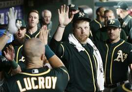 Oakland Athletics starting pitcher Brett Anderson, center, congratulates Jonathan Lucroy after he scored against the Texas Rangers during the seventh inning of a baseball game Monday, July 23, 2018, in Arlington, Texas. (AP Photo/Mike Stone)