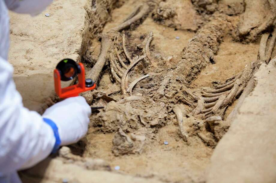 Archeologist David Givens uses a precise survey to tool to map remains that scientists are working to identify. Photo: Photo For The Washington Post By Timothy C. Wright / For The Washington Post