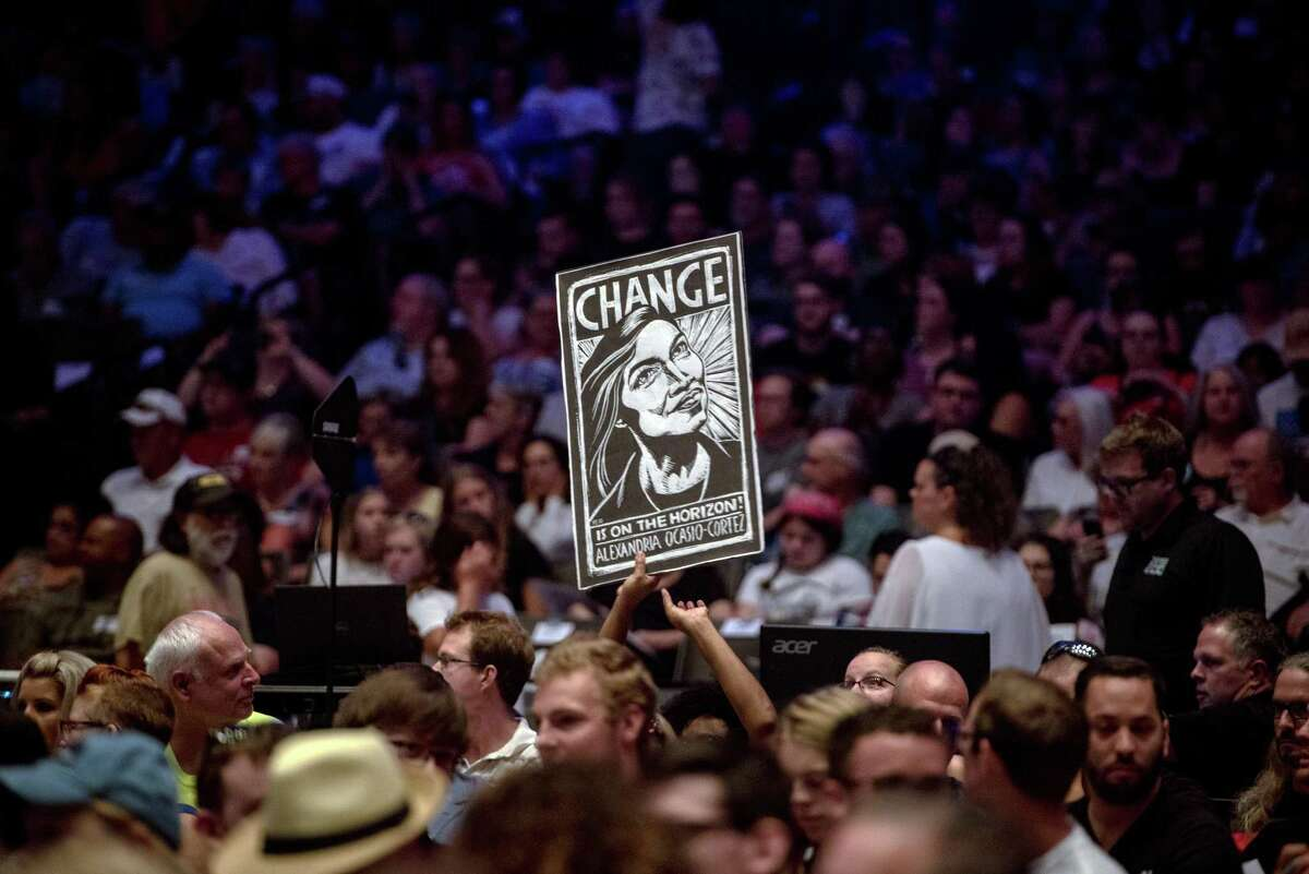 A supporter holds a sign depicting Alexandria Ocasio-Cortez as she speaks at a campaign event for James Thompson, a Kansas House candidate, in Wichita on Friday, July 20, 2018. Less than four weeks after scoring a stunning upset in a Democratic House primary in New York, Ocasio-Cortez stepped out onto the national campaign stage for the first time to take her message to the heartland. (Hilary Swift/The New York Times)