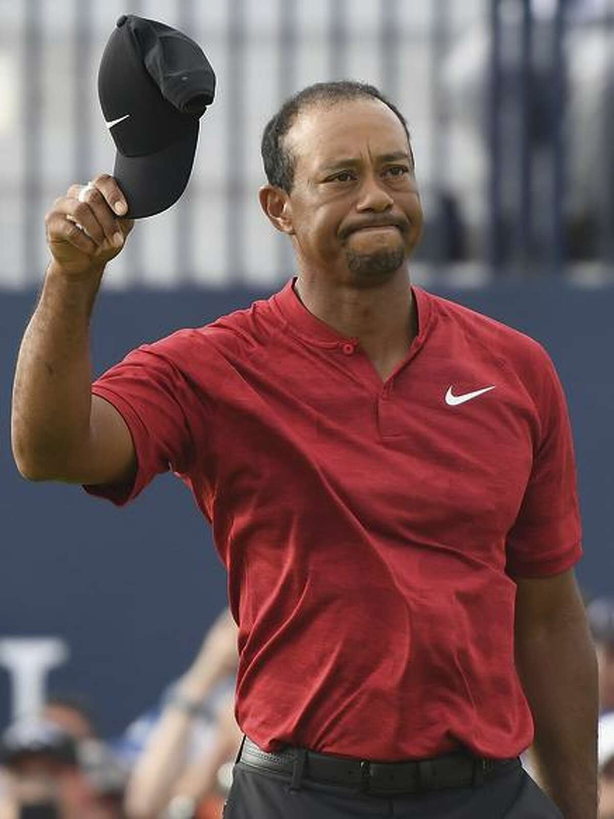 Tiger Woods acknowledges fans on the 18th green of the British Open Sunday.