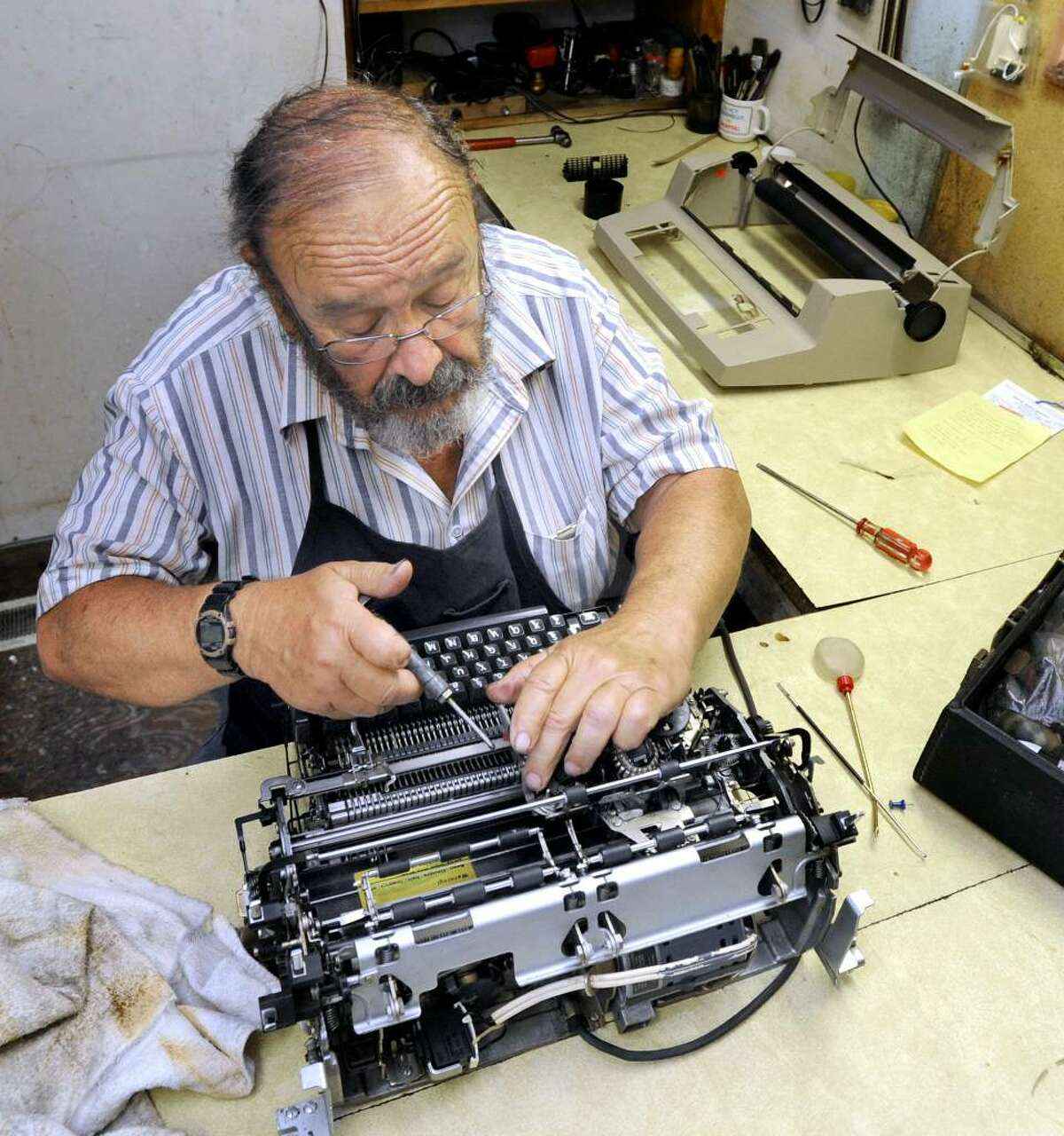 David Morrill gives a tune-up to a 1972 IBM Selectric typewriter that is still used by its owner.