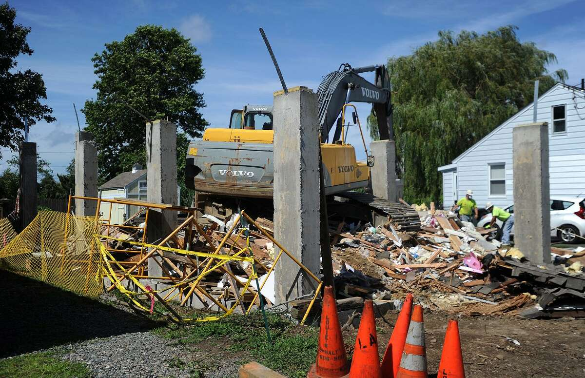 A home at 24 Cooper Avenue in Milford, Conn is demolished on Tuesday, July 24, 2018 after it collapsed while being raised on to new concrete pilings on Monday.