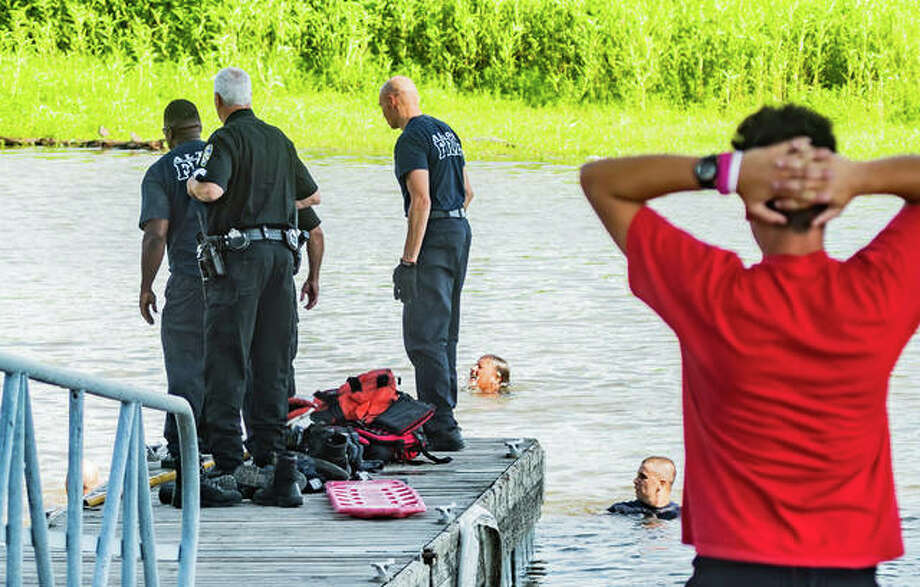 A young boy, right, nervously puts his hands to his head while Alton firefighters and police officers work to find a boy who fell into Alton Marina Monday evening. Photo:       Nathan Woodside | The Telegraph