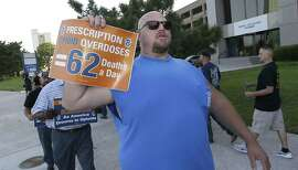 Clint Powell, of Keller, Texas, marches with other Teamsters as they protest outside the McKesson Corp. shareholders meeting in Irving, Texas, Wednesday, July 26, 2017. McKesson Corp. is the largest US distributor of prescription drugs. (AP Photo/LM Otero)