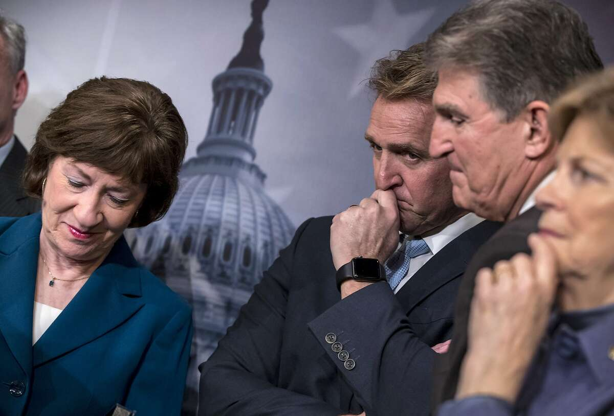 From left, Sen. Susan Collins, R-Maine, Sen. Jeff Flake, R-Ariz., Sen. Joe Manchin, D-W.Va., and Sen. Jeanne Shaheen, D-N.H., finish a news conference on the bipartisan immigration deal they reached during a news conference at the Capitol in Washington, Thursday, Feb. 15, 2018. The Trump administration is already denouncing their deal in the Senate, saying it will