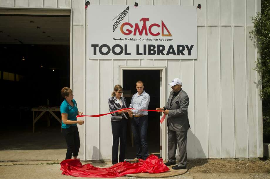 From left, Stephanie Davis, vice president of the Greater Michigan Construction Academy, Sharon Mortensen, president of the Midland Area Community Foundation, Jeff Havens and Jimmy Greene, CEO of the GMCA, cut a ribbon during an event celebrating GMCA's new tool library on Tuesday, July 24, 2018 in Midland. (Katy Kildee/kkildee@mdn.net) Photo: (Katy Kildee/kkildee@mdn.net)