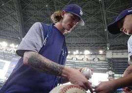Milwaukee Brewers relief pitcher Josh Hader signs autographs before a baseball game against the Los Angeles Dodgers Sunday, July 22, 2018, in Milwaukee. (AP Photo/Morry Gash)