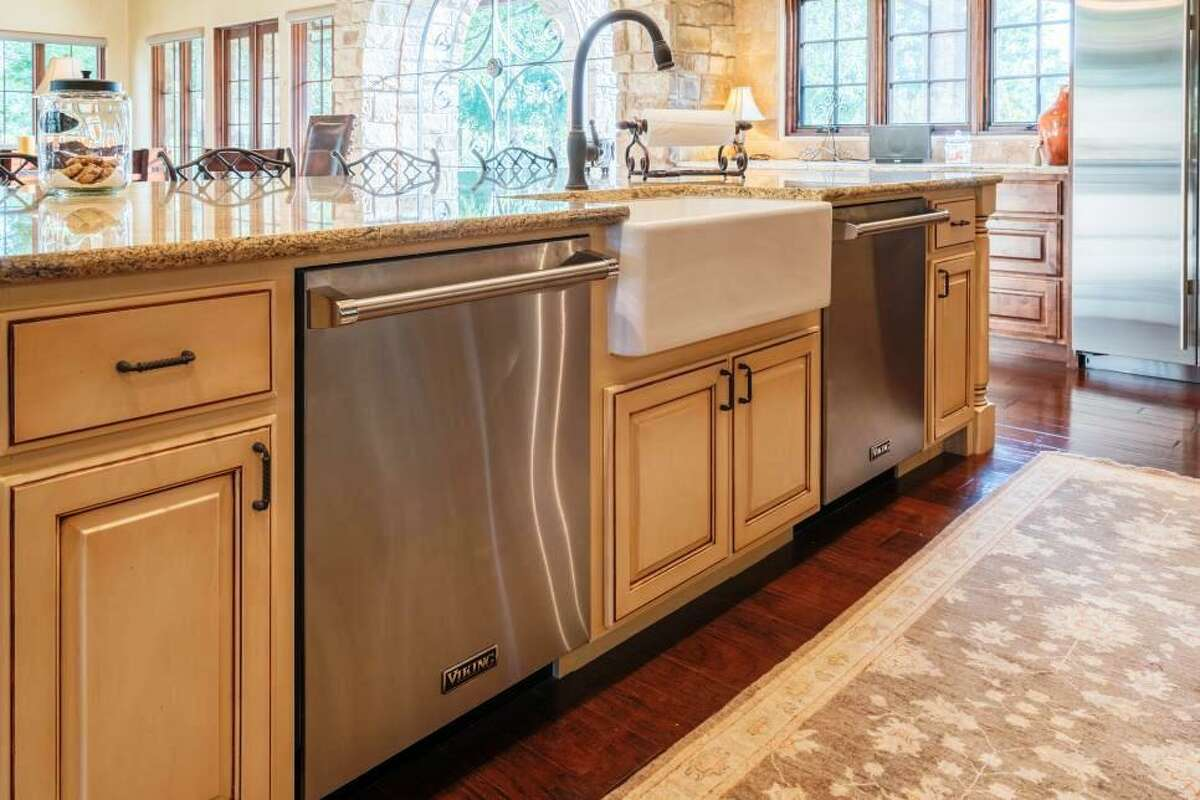 For homeowners who love to entertain, dual dishwashers -- here efficiently set into the cabinets on either side of the sink -- are very desirable features. There's enough room to throw in all the pots, pans, dishes and glassware they?'ve used and get it all cleaned at once.