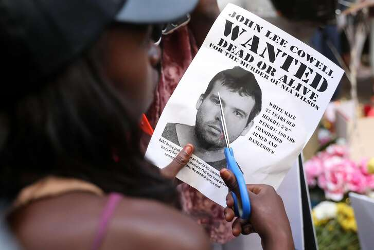 A young woman, who didn't want to be identified, cuts a wanted poster of John Lee Cowell during a vigil in memory of stabbing victim Nia Wilson at McArthur BART Station in Oakland, Calif. on Monday, July 23, 2018.