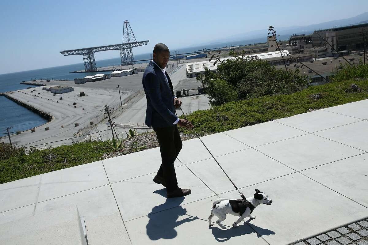 Theo Ellington, a resident at the new Shipyard housing, walks his dog LeRoy, Thursday, April 26, 2018, in San Francisco, Calif.