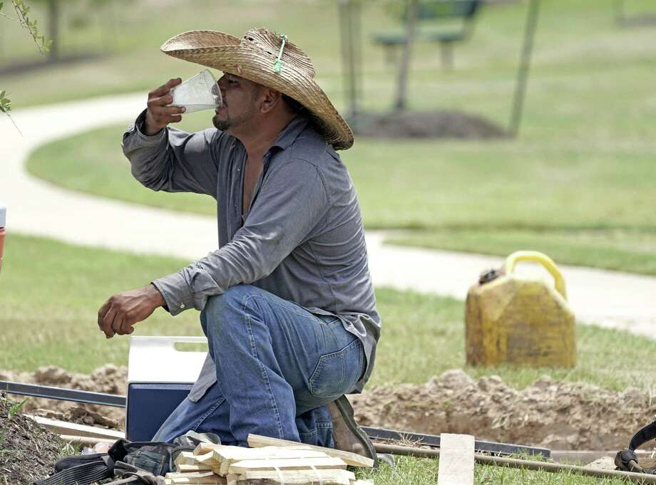 Construction worker Ramiro Montez drinks water while taking a break from working Monday, July 23, 2018, in Houston. Houston is on pace to use more water than any month since the drought of 2011.   Keep clicking to see Harris County businesses who had the largest water bills last year.   Photo: David J. Phillip, STF / Associated Press / Copyright 2018 The Associated Press. All rights reserved