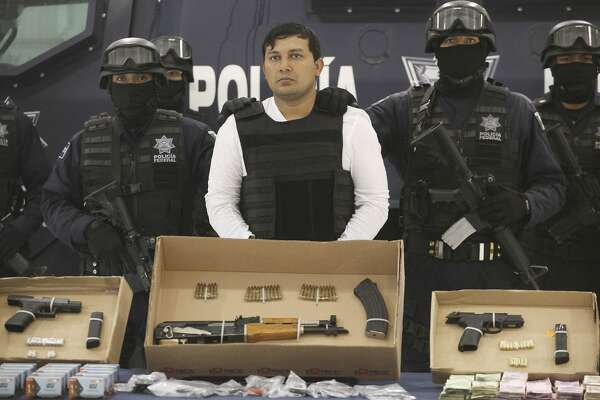 "Federal Police agents present Jesus Enrique Aguilar, alias ""El Mamito"", center, to the media in Mexico City, Monday July 4, 2011. Police believe Aguilar is connected with the killing of a U.S. Immigration and Customs Enforcement agent. Aguilar is a former member of the Mexican Army and allegedly a co-founder of the Zetas drug cartel, according to authorities. (AP Photo/Alexandre Meneghini)"