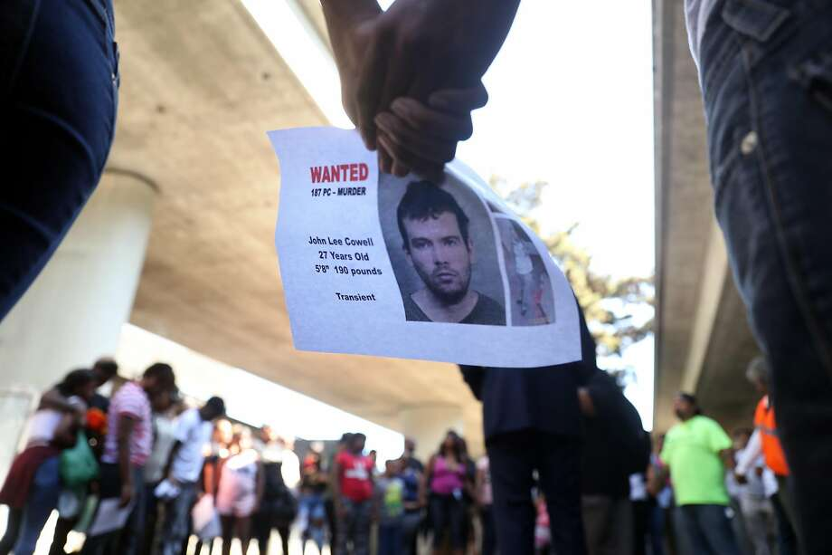 Two people hold a wanted poster for John Lee Cowell during a prayer circle at a vigil in memory of stabbing victim Nia Wilson at McArthur BART Station in Oakland, Calif. on Monday, July 23, 2018. Photo: Scott Strazzante / The Chronicle