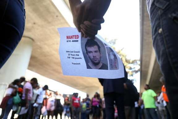Two people hold a wanted poster for John Lee Cowell during a prayer circle at a vigil in memory of stabbing victim Nia Wilson at McArthur BART Station in Oakland, Calif. on Monday, July 23, 2018.