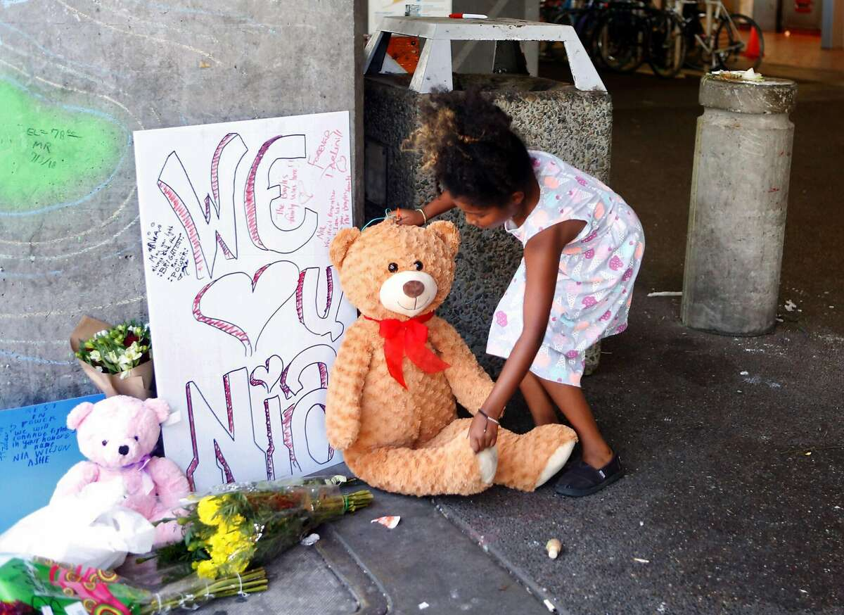 Sterling Moss, of Berkeley, leaves a teddy bear at the MacArthur BART station on July 24, 2018 for Nia Wilson, who was stabbed there on Sunday.