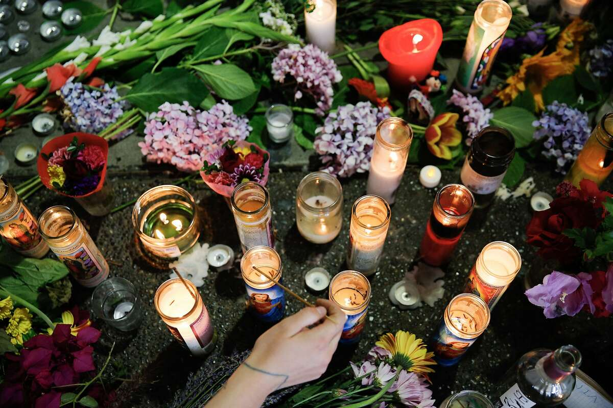 Susanna McIntyre lights candles at the memorial for Nia Wilson at the MacArthur BART Station, Tuesday, July 24, 2018, in Oakland. Calif. Wilson, 18, was stabbed Sunday at the MacArthur BART Station and died from her injuries. The suspect in the slaying fled and was found on a train a day later.
