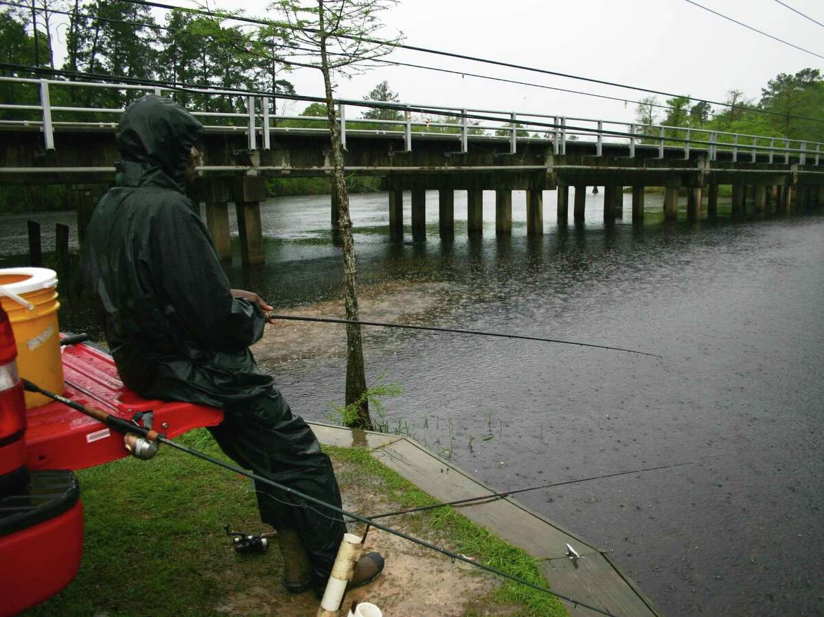 Houston resident and retired longshoreman Jack Crosby Jr. ignores the rain March 20 and focuses on catching bass, white perch and catfish in Huffman's Luces Bayou while a flood watch is in effect.