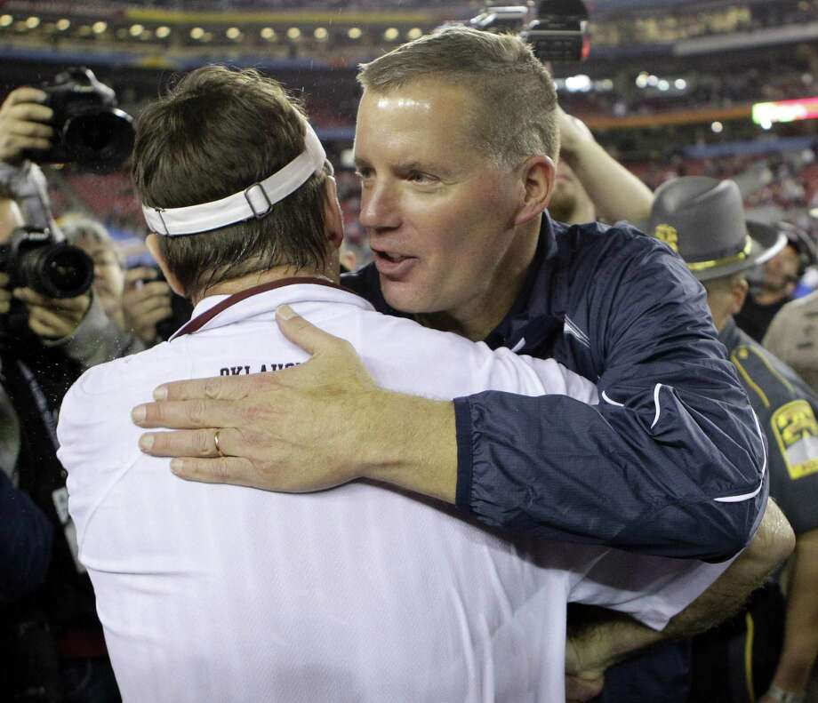 UConn coach Randy Edsall, right, embraces Oklahoma coach Bob Stoops after Oklahoma defeated UConn in the Fiesta Bowl on Jan. 1, 2011, in Glendale, Ariz. Oklahoma won 48-20. Photo: Matt York / Associated Press / AP2011