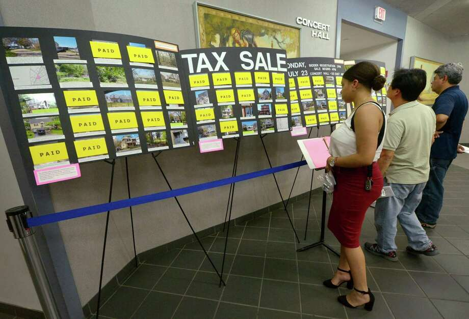 People, including Natalie Rodriguez, left, look over the Tax Sale properties on July 5 at Norwalk City Hall. Photo: Erik Trautmann / Hearst Connecticut Media / Norwalk Hour