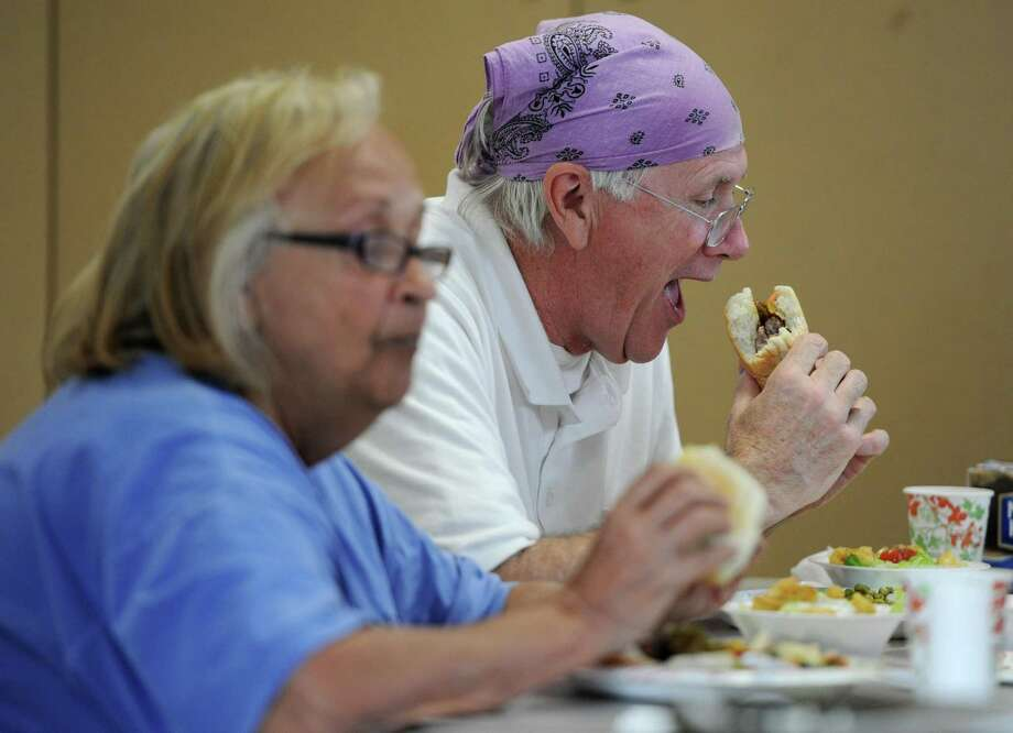 New Milford residents Penny and James O'Gorman enjoy dinner at Loaves & Fishes Hospitality in New Milford in May 2014. The pantry feeds the hungry in New Milford and typically gives out between 25 and 30 meals per day. Loaves & Fishes is entirely volunteer-run and gives out donated food with no state or federal funding. Photo: Tyler Sizemore / Tyler Sizemore / The News-Times