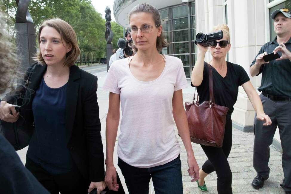 Clare Bronfman, center, leaves federal court, Tuesday, July 24, 2018, in the Brooklyn borough of New York. Bronfman, an heiress to the Seagram's liquor fortune and three other people were arrested on Tuesday in connection with the investigation of a self-improvement organization accused of branding some of its female followers and forcing them into unwanted sex.