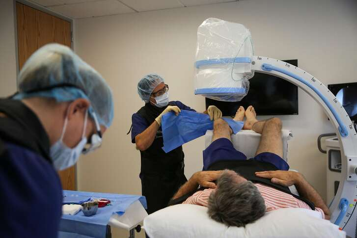 Dr. Paul Handleman (second from left) and nurse Jessica Vanderbyl (left) prepare patient Jon Brandstad (right) for a stem cell procedure at the Health Link Medical Center in San Rafael, Calif., on Monday, Sept. 18, 2017.
