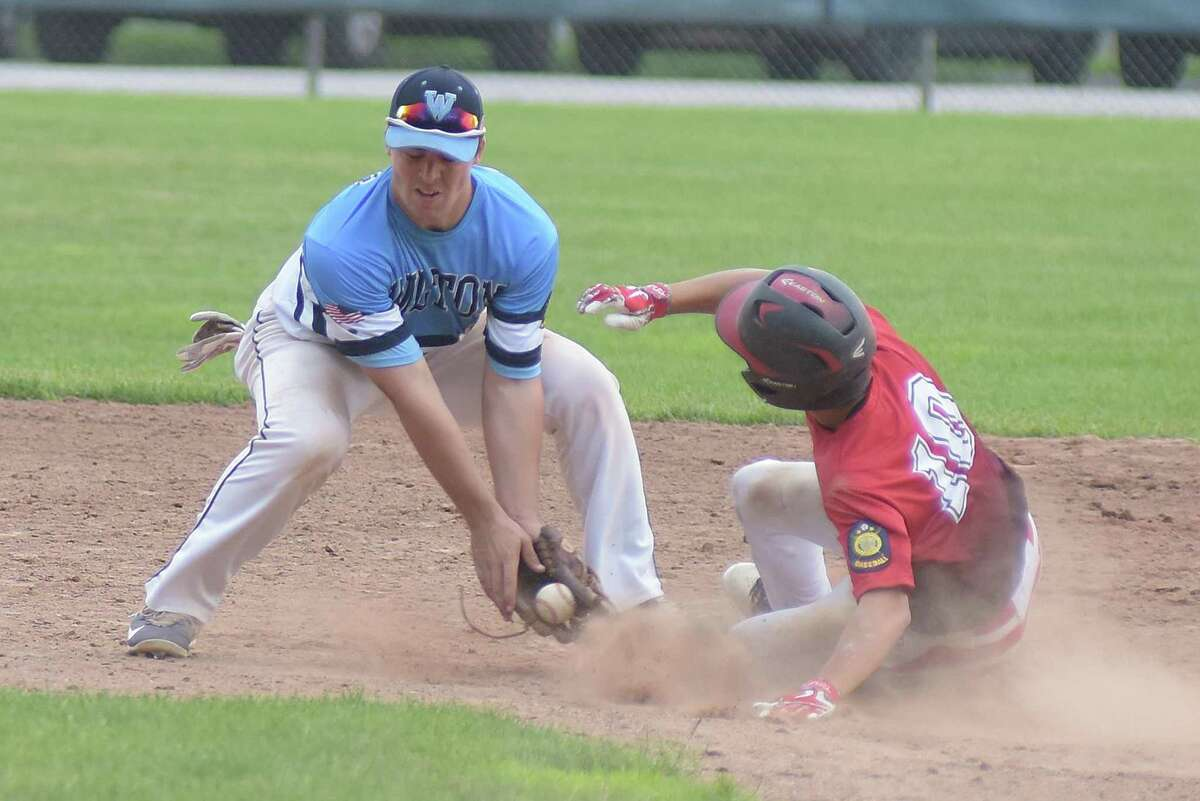Wilton Post 86 shortstop Collin Kahal, left, puts a late tag down on Waterbury Post 1 base runner John Castro on a stolen base in Tuesday's American Legion state tournament game at Wilton High School.