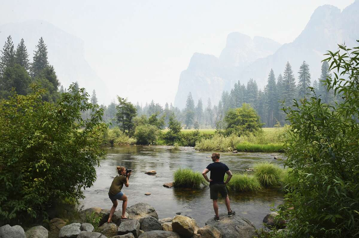 German tourists Stephanie Schultz, left, photographs Kai Rudolph, right, along the Merced River in Yosemite Valley as smoke from the Ferguson Fire hangs in the air Tuesday, July 24, 2018, in Yosemite National Park, Calif. The heart of Yosemite National Park, where throngs of tourists are awe-struck by cascading waterfalls and towering granite features like El Capitan and Half Dome, will be closed as firefighters try to corral a huge wildfire just to the west that has cast a smoky pall and threatened the park's forest, officials said Tuesday. The closure is expected to last through Sunday. (Eric Paul Zamora/The Fresno Bee via AP)