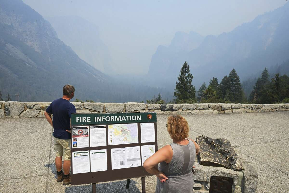 Smoke from the Ferguson Fire fills Yosemite Valley as seen from Tunnel View Tuesday, July 24, 2018, in Yosemite National Park, Calif. A Yosemite National Park official says at least a thousand campground and hotel reservations will be canceled after authorities decided to close Yosemite Valley to keep a growing forest fire at bay. Spokesman Scott Gediman says the valley, the heart of the visitor experience at the park, along with a windy, mountainous, 20-mile (32-kilometer) stretch of State Route 41 that is part of Yosemite will close beginning Wednesday at noon. (Eric Paul Zamora/The Fresno Bee via AP)