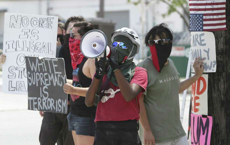 Demonstrators shout messages of protest directed at personnel in the ICE processing facility at 3523 Crosspoint in San Antonio on Tuesday. They've been camping at there for a week. Photo: Tom Reel /Staff Photographer / 2017 SAN ANTONIO EXPRESS-NEWS
