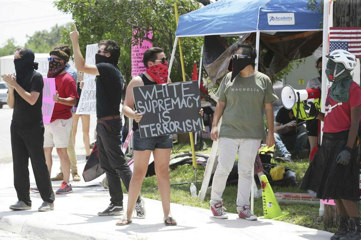 Demonstrators shout messages of protest directed at personnel in the ICE processing facility at 3523 Crosspoint in San Antonio on Tuesday.